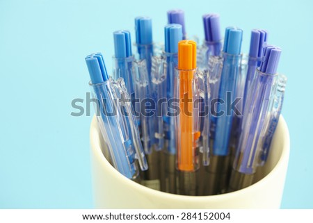 shooting different kinds of pens isolated on blue background - stock photo