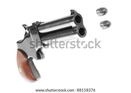 Shooting hand gun (2 shot .45 cal derringer) with two flying bullets. Close up with shallow DOF.