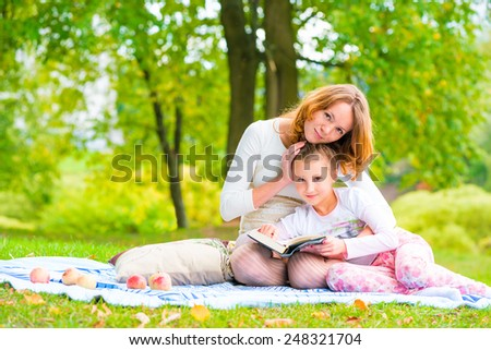 Shooting mother and daughter in the park on a picnic - stock photo