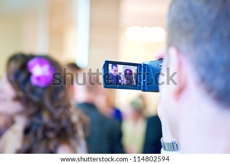 Shooting on video camera. Focus on camera. - stock photo