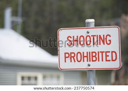 Shooting prohibited sign on pole outdoor with blurred background of residential house and copy space. - stock photo