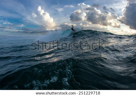 Shooting surfing in the waves of the Indian Ocean on the island of Mauritius against the beautiful sunset and clouds. The photo was taken from the water. - stock photo