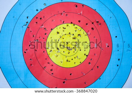 Shooting target and bulls eye with holes, drilled background - stock photo