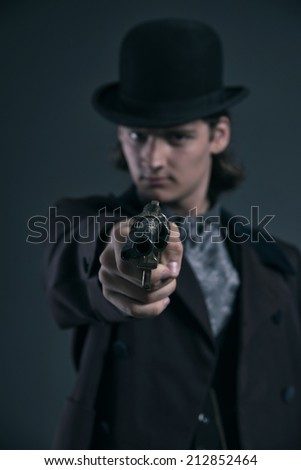 Shooting western 1900 fashion man with brown hair and hat. Studio shot against grey. - stock photo