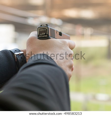 Shooting with a pistol. Man aiming pistol in shooting range.
