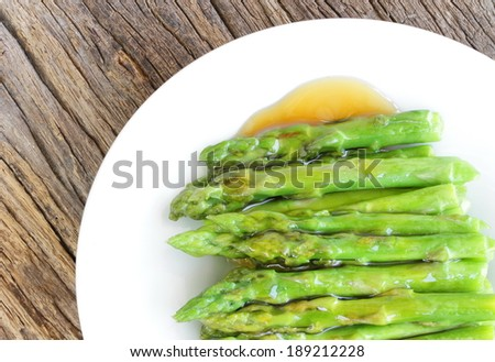Shoots of fresh green asparagus fried in oyster sauce with delicious hot gunships deployed in a white dish ready to eat. - stock photo