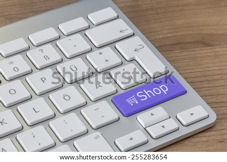 Shop and a shopping cart symbol on a large blue button of a modern keyboard on a wooden desktop - stock photo