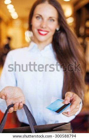 Shop assistant handing a card to a customer (soft focus on a card) - stock photo