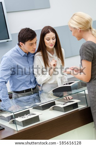 Shop assistant helps couple to select jewelry at jeweler's shop. Concept of wealth and luxurious life - stock photo