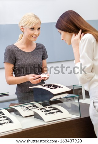Shop assistant helps lady to choose jewelry at jeweler's shop. Concept of wealth and luxurious life - stock photo
