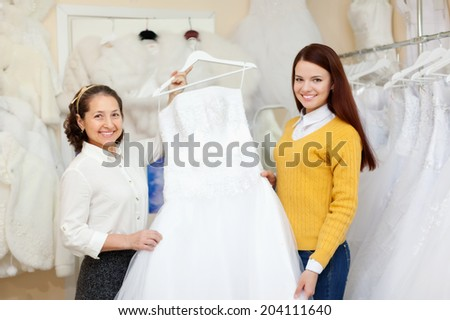 Shop assistant  helps the bride in choosing bridal dress at shop of wedding fashion - stock photo