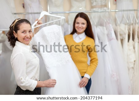 Shop assistant  helps the bride in choosing bridal dress at shop of wedding fashion. Focus on mature - stock photo