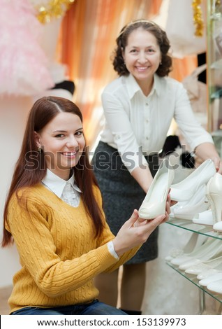 Shop assistant helps to girl chooses white shoes at shop of wedding fashion