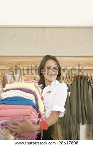 Shop assistant holding a pile of clothes in a fashion store - stock photo
