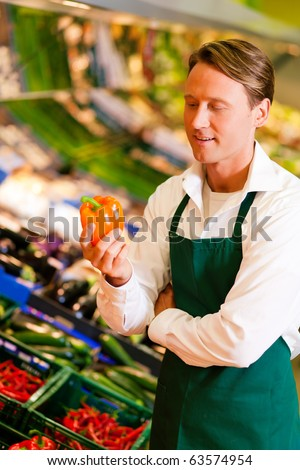 Shop assistant in a supermarket at the vegetable shelf checking the stuff for sale