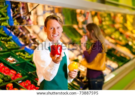 Shop assistant in a supermarket at the vegetable shelf; in the background a woman choosing vegetables - stock photo