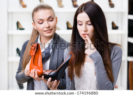 Shop assistant offers pumps for the female customer in the shopping center - stock photo