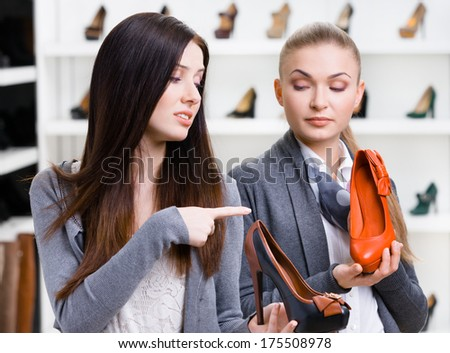 Shop assistant offers stylish pumps for the female customer in the shopping center - stock photo