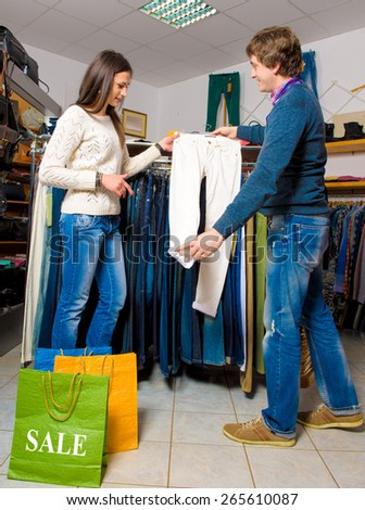 Shop assistant showing white jeans to beautiful girl in the store