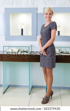 Shop assistant stands near the window case at jeweler's shop. Concept of wealth and luxurious life - stock photo