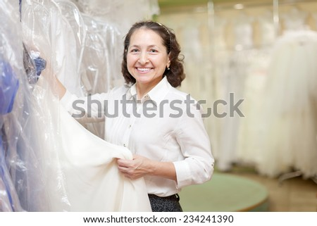 Shop assistant with bridal dress at wedding store