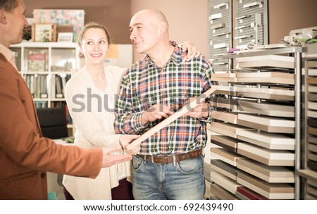 shop assistant working with smiling customer in kitchen furniture store