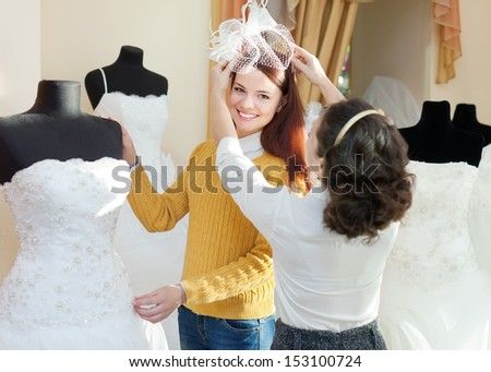 shop consultant helps girl chooses white bridal outfit at shop of wedding fashion. Focus on bride - stock photo