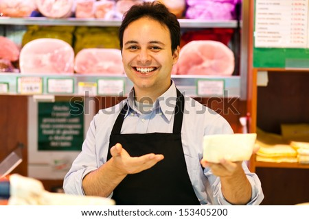 Shop keeper serving cheese - stock photo