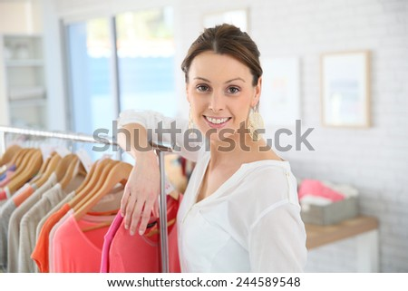 Shop woman standing by clothes in store - stock photo