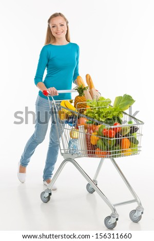Shopaholic. Cheerful young woman carrying shopping cart full of goods and smiling while isolated on white