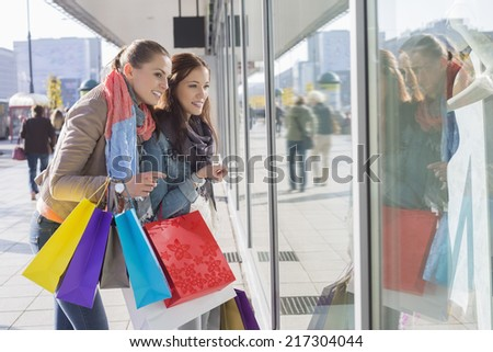 Shopaholic female friends window shopping