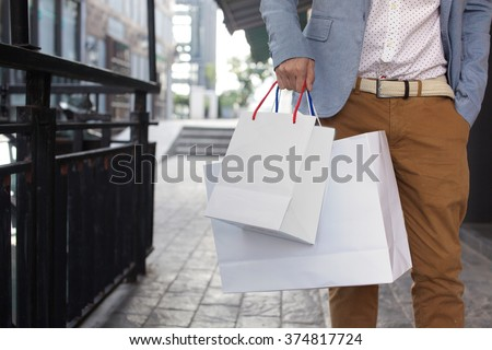 Shopaholic man walking on commercial street with a lot of shopping bags - stock photo