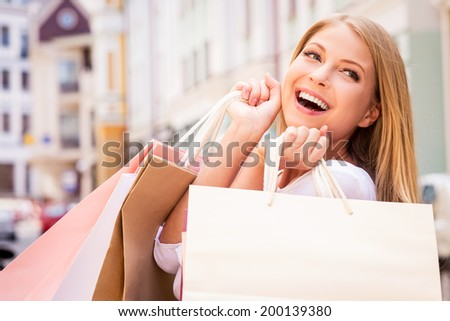 Shopaholic woman. Beautiful young cheerful woman holding shopping bags and expressing positivity while standing outdoors - stock photo