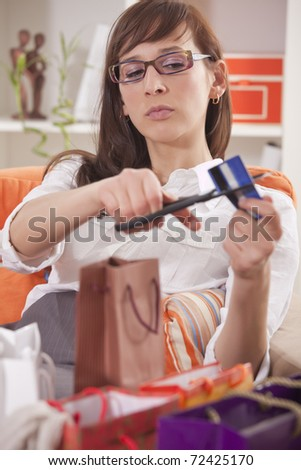 shopaholic woman with shopping bags cutting her credit card - stock photo