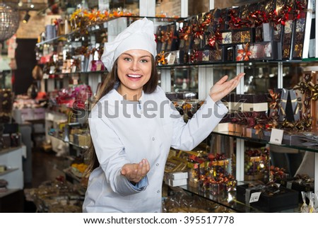 shopgirl posing with delicious chocolate and confectionery at display