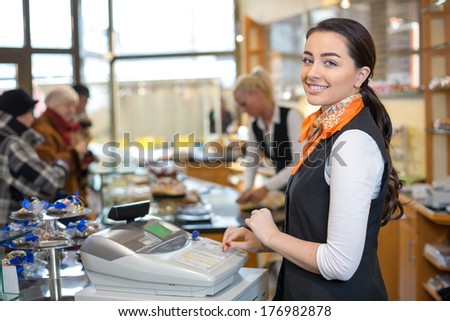 Shopkeeper and saleswoman at cash register or checkout counter - stock photo