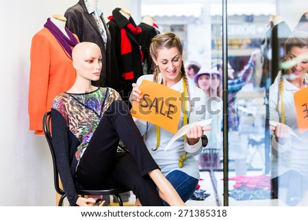 Shopkeeper working at promotion putting sale sign in shop window - stock photo