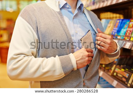 Shoplifter stealing bar of chocolate in a supermarket - stock photo