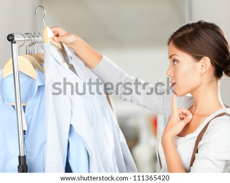 Shopper woman choosing clothes thinking looking at clothing while shopping in store. Beautiful young multiracial Caucasian Asian young woman model. - stock photo