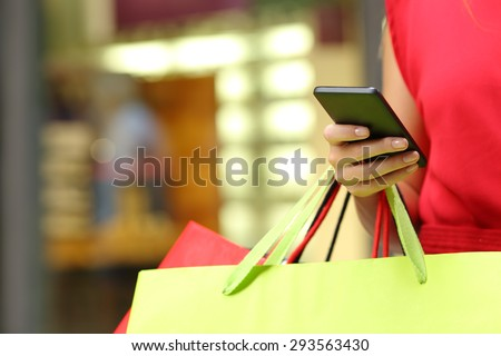 Shopper woman hand shopping with a smart phone and carrying bags - stock photo