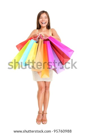 Shopper woman holding shopping bags standing happy smiling and excited in full body isolated on white background. Beautiful multiracial Chinese Asian / Caucasian female model joyful. - stock photo
