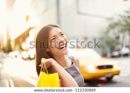 Shopper woman on Manhattan, New York City shopping having fun laughing outside in streets of New York. Fresh blissful mixed race Asian / Caucasian girl holding shopping bag.