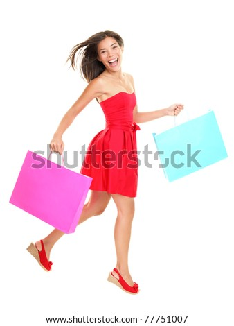 Shopper - woman shopping holding shopping bags in red summer dress. Young asian woman walking cheerful and smiling isolated in full body on white background. Mixed race Asian / Caucasian female model.
