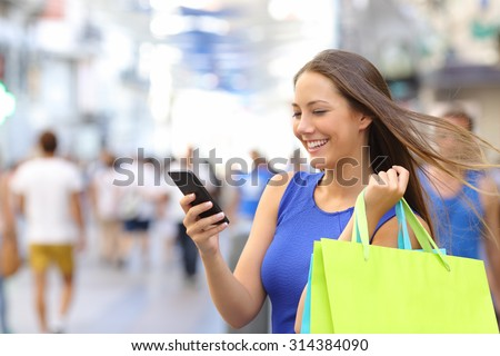 Shopper woman shopping with a smartphone in a commercial street - stock photo
