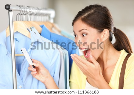 Shopper woman surprised over sale price. Happy Asian shopping woman surprised over rebate prices looking at price tag on clothes. Mixed race Asian chinese / Caucasian young female model. - stock photo