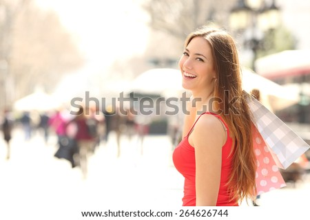 Shopper woman walking and shopping in the street in summer holding bags - stock photo