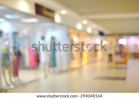 Shoppers at shopping center, motion blur. Blurred background of shopping center corridor - stock photo