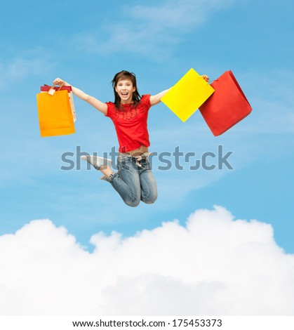shopping and motion concept - happy girl with shopping bags