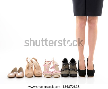 Shopping and sale. Female legs with shoes assortment, young woman put shoes on in shop and makes her choice, front view. Over white background - stock photo