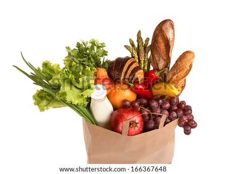 Shopping bag filled with groceries / studio photography of assorted foods in brown grocery bag isolated over white background